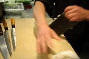 Положите немного риса на бамбуковую циновку с нори